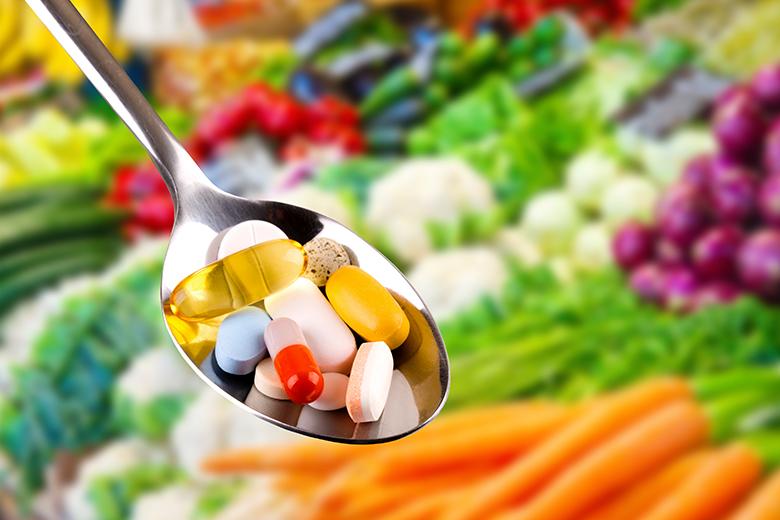 Auf einem Löffel liegen verschiedene bunte Tabletten und Kapseln, im Hintegrund sieht man Obst und Gemüse