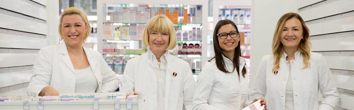 Die Apothekerinnen der Christinen Apotheke stehen in der Ladenstraße und lächeln